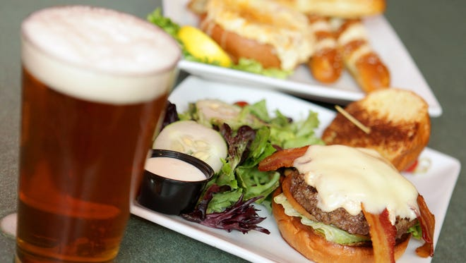 The Greene Turtle has burgers with Old Bay and topped with crab dip, smoked bacon and American cheese,