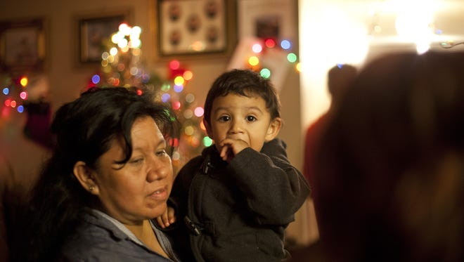 A grandmother holds her grandson as volunteers form the Washington County School District deliver gifts to families in need Tuesday, Dec. 23, 2014. In order to stay out of the cold and have access to resources like showers, two or three families will pair up in two to three bedroom apartments.