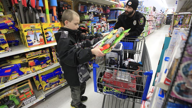 Ryan Newport, 11, shops with Daleville Police officer James King Jr. on Dec. 20 2014 during Daleville's Operation Christmas at Walmart North in Muncie. Ryan Newport, 11, shops with Daleville Police officer James King Jr. Saturday afternoon for Daleville's Operation Christmas at the McGalliard Wal-Mart in Muncie. The program helped 13 families give Christmas gifts to their kids.