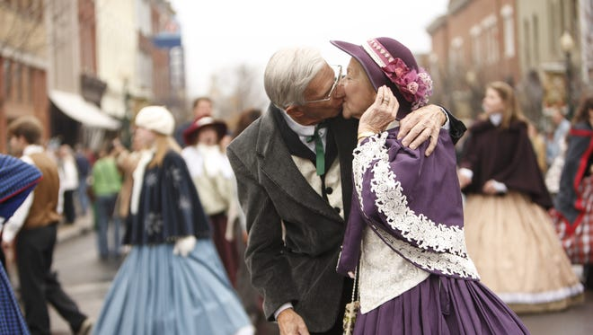 A senior couple kiss on Main Street during the Dickens of a Christmas festival in Franklin.