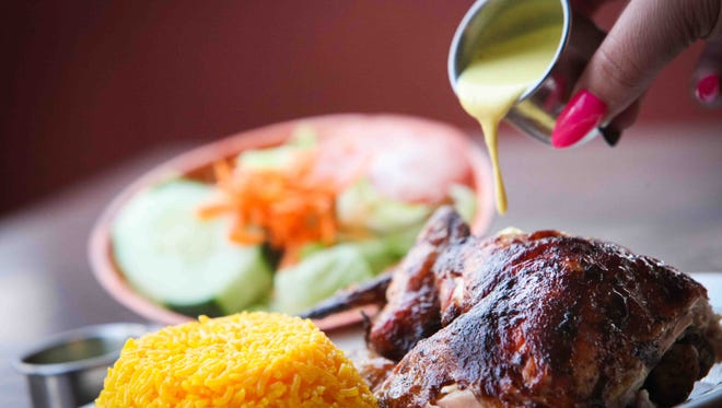 At The Chicken House Peruvian Cuisine, a half chicken is served with yellow rice and house salad. The spicy yellow chile pepper aji sauce always accompanies the chicken.