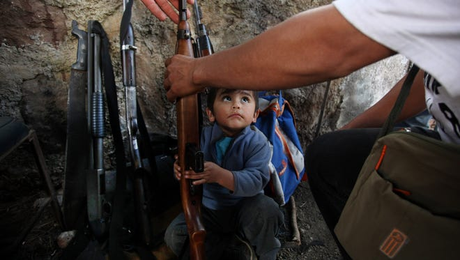FILE - In this Jan. 16, 2014 file photo, a child helps his father arrange weapons at a checkpoint set up by the Self-Defense Council of Michoacan, in Tancitaro, Mexico.