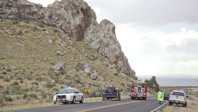 Firefighters extinguish what is left of a burning car found on Old Highway 91 on Friday, Sept. 26, 2014. The remote roadway is undergoing an extensive improvement project in the first half of 2017 in an effort to address safety concerns.
