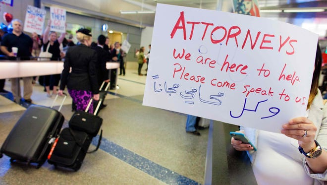 Volunteer lawyers hold signs offering help to people at Los Angeles International Airport following President Trump's executive order banning citizens from seven predominantly Muslim countries from entering the U.S.