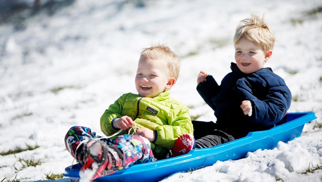 On March 12, 2017, the first morning of Daylight Saving Time, area residents woke up to a snowy scene. Henry Davis, 3, left, and Brooks Hutchins, 2, enjoyed the snow by sledding at West Asheville Park.