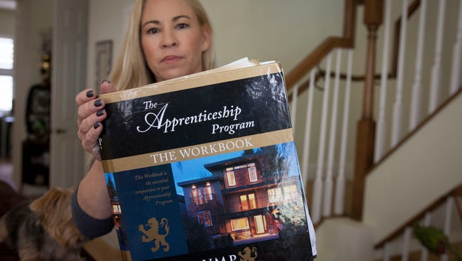 "3/23/16--KJ-Fort Lauderdale, FL--Sherri Simpson holds up a book of class materials she received when she started the Trump University program on real estate investing. She went to a free seminar then went on to sign up for the extended ""elite"" level program for $35,000 which was supposed to be a year-long program to get her going in the real estate market. She is now a plaintiff in a California class action lawsuit along with New York Attorney General Eric Schneiderman's case against the educational enterprise."