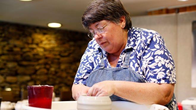 Lynn Jenkins creates pottery at the Folk Art Center.
