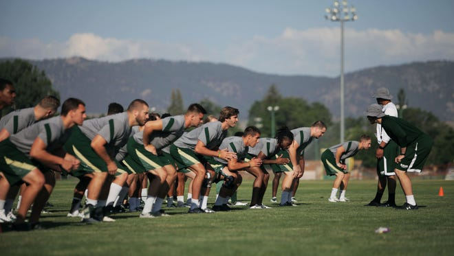 CSU football players warm up before practice on June 27, 2017, on the Colorado State University Intramural Fields