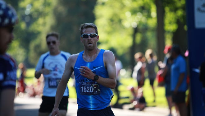 Sean Wilde finishes as the men's overall winner during the FireKracker 5k with a time of 16:42 at City Park on Tuesday, July 4, 2017.