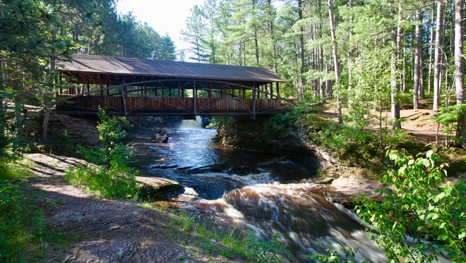 A footbridge crosses the river between Upper and Lower Amnicon Falls at Amnicon Falls State Park near South Range.