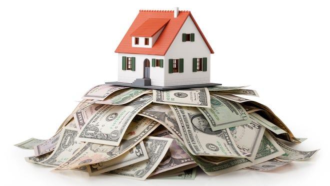 Model house standing on a heap of dollar bills.