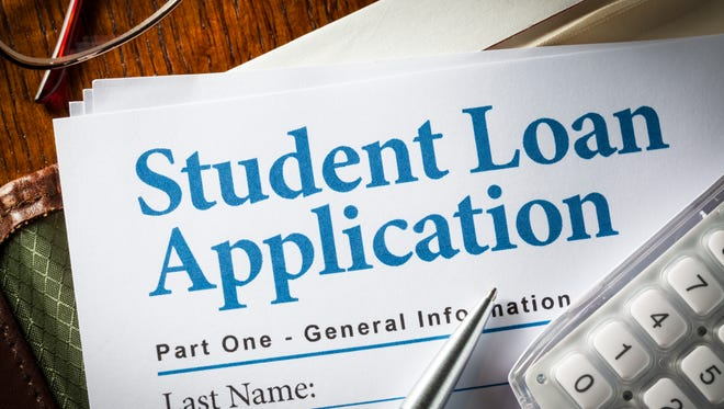 Student Loan Application with pen, calculator and glasses