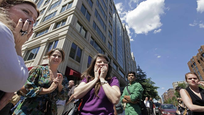 Office workers gather on the sidewalk in downtown Washington, Tuesday, Aug. 23, 2011, moments after a 5.9 magnitude tremor shook the nation's capitol. The earthquake centered northwest of Richmond, Va., shook much of Washington, D.C., and was felt as far north as Rhode Island and New York City.