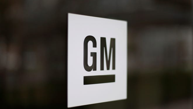 This Friday, May 16, 2014, file photo, shows the General Motors logo at the company's world headquarters in Detroit.  General Motors says it is making the first mass-production autonomous car without a steering wheel or pedals. The company says it has filed a petition with the federal government seeking permission to put the vehicles on the road sometime next year with no human backup drivers. GM's Cruise Automation unit has announced plans to carry passengers in self-driving cars that won't have a backup driver in 2019. (AP Photo/Paul Sancya, File)