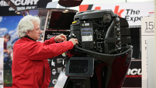 Howard Fink of Hubertus looks over the wiring on a Mercury 150-horsepower outboard with the cowling off at a Milwaukee Journal Sentinel Boat Show.