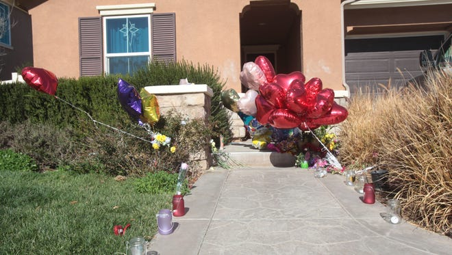 Candles and balloons stand outside of a Perris house where authorities say 13 victims were held by abusive parents David and Louise Turpin.