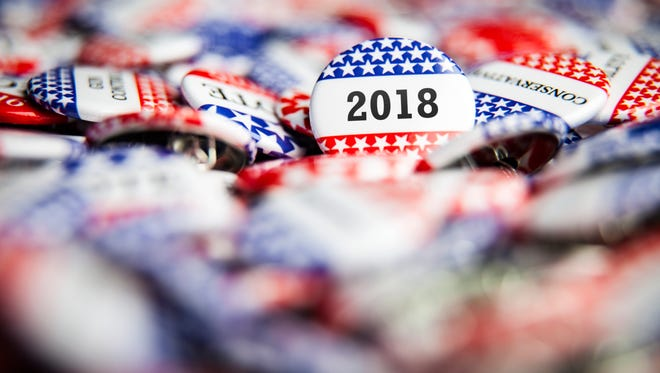 A stock photo showing 2018 campaign buttons.