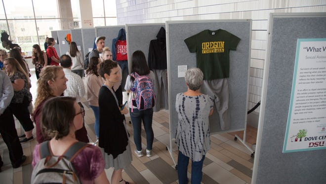 "Representatives from the Dove Center and the DSU Women's Resource Center display clothes worn by sexual assault victims in a project titled ""What Were You Wearing?"" Monday, April 2, 2018."