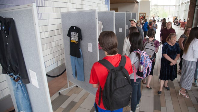 """Representatives from the Dove Center and the DSU Women's Resource Center display clothes worn by sexual assault victims in a project titled """"What Were You Wearing?"""" Monday, April 2, 2018."""