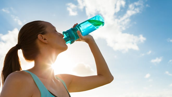 File art of a woman drinking water. It's important to stay hydrated because of added sweat loss in hot weather.