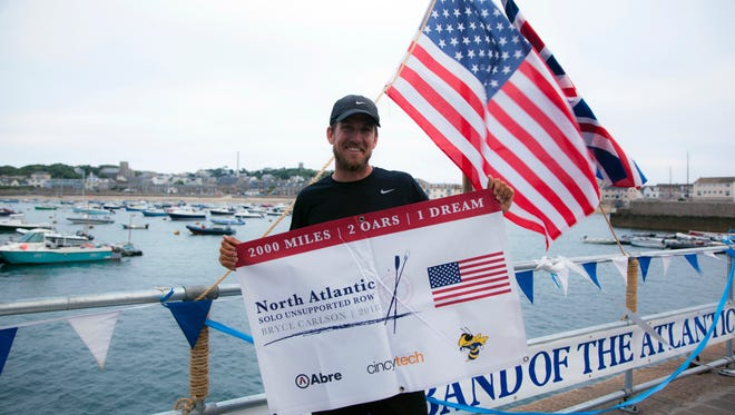 In this Saturday, Aug. 4, 2018, photo provided by Bryce Carlson Adventures, Bryce Carlson poses for a photo after completing his solo unsupported row across the Atlantic, at St Mary's Harbour, Isle of Scilly, England.