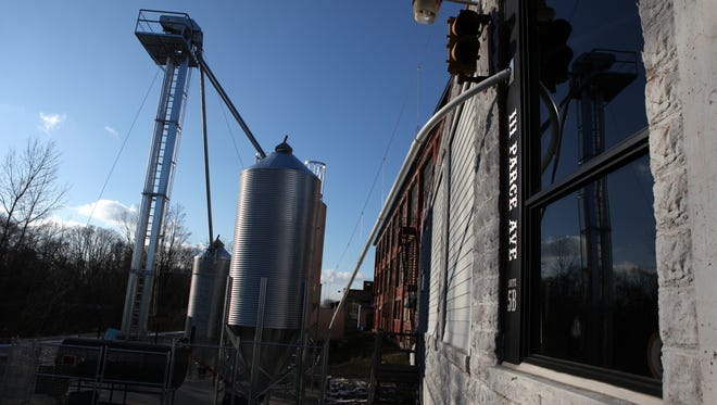 Wheat storage and smoker outside Iron Smoke Whiskey, a distillery in Fairport.