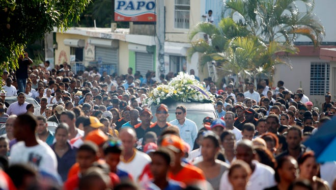 People march as a car carries the coffin containing the body of Oscar Taveras during his funeral procession in Sosua.