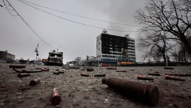 Shells and a burned police car are scattered on an empty square outside a burned-out publishing house in central Grozny, Russia, Thursday, Dec. 4, 2014.  A gun battle broke out early Thursday in the capital of Russia's North Caucasus republic of Chechnya, puncturing the patina of stability ensured by years of heavy-handed rule by a Kremlin-appointed leader. The violence erupted hours before Russian President Vladimir Putin began his annual state of the nation address in Moscow. (AP Photo/Musa Sadulayev)
