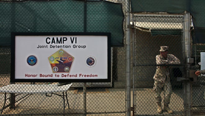 In this file photo taken Tuesday May 12, 2009 and  reviewed by the U.S. military, a soldier stands guard at the front gate entrance to Guantanamo's Camp 6 maximum-security detention facility, at Guantanamo Bay U.S. Naval Base, Cuba. The U.S. government said Sunday Dec. 7, 2014 six men who have been held more than 12 years at Guantanamo Bay have been sent to Uruguay to be resettled as refugees.