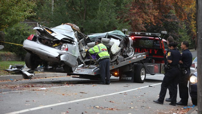 Yonkers police stand by as workers with County Towing remove a car involved in a fatal car crash overnight on Rumsey Road near Valley Road in Yonkers on Sunday, Oct. 19, 2014. A 28-year-old Yonkers woman was killed and the driver was injured.