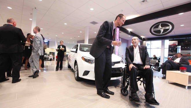 Toyota World owner Warren Price (right) chats with Brian Tharan as the dealership celebrates its grand opening gala last month at its new location on Cleveland Avenue in Newark.