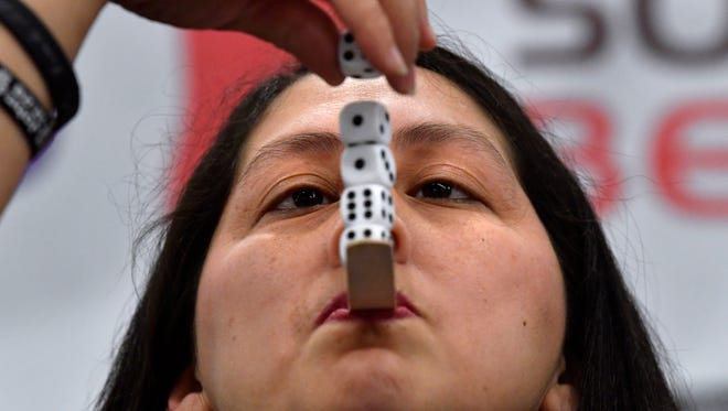 """Suzanna Daniels of MetroCare Services holds a tongue depressor in her mouth and balances dice upon it during a game at the 2018 Business EXPO Wednesday. Held at the Abilene Convention Center, this year's game show-like theme was """"Let's Make a Deal."""""""
