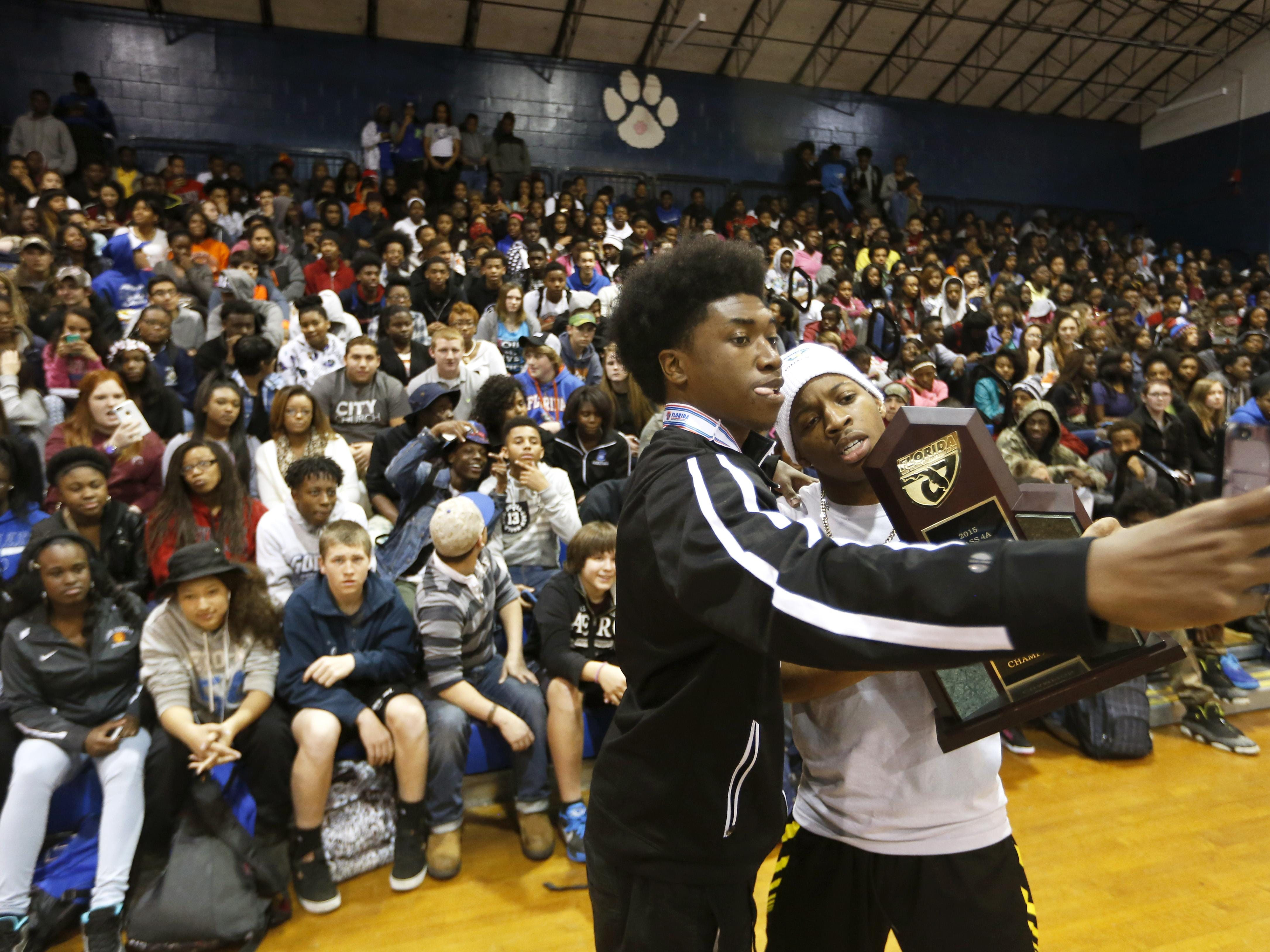 Jordan Gaskins, left, and BJ Gant-McClenton take a selfie with the Godgy High School boy's basketball state championship trophy during their celebration at the school on Friday.