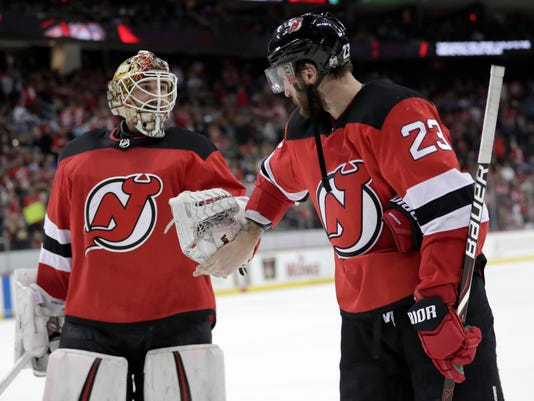 New Jersey Devils goaltender Keith Kinkaid, left, and right wing Stefan Noesen talk at the end of the second period of an NHL hockey game, Saturday, March 31, 2018, in Newark, N.J. The Devils won 4-3. (AP Photo/Julio Cortez)