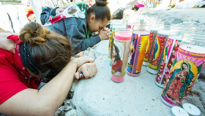 """Lové Olmeda, 15, background, and Jovonnie Pacheco, 19,  become emotional while praying at the alter on top of Totugas """"A"""" Mountain on Sunday, Dec. 11, 2016, during the annual Tortugas pilgrimage."""