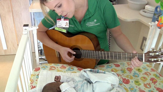 Bridget Sova, music therapist at the Helen DeVos Children's Hospital, sings to Aubrey Spearman in the infant's room at the hospital in Grand Rapids, Mich.