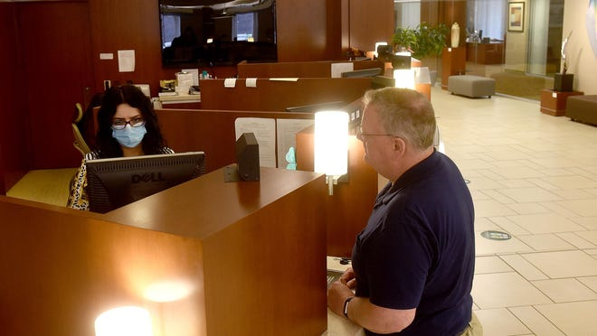 Central Bank of Boone County teller Lana Torseen helps customer Kenneth Mohr with a banking transaction. Banking lobbies have reopened with other businesses and customers are likely to encounter tellers with masks or newly installed barriers to help prevent spread of COVID-19.