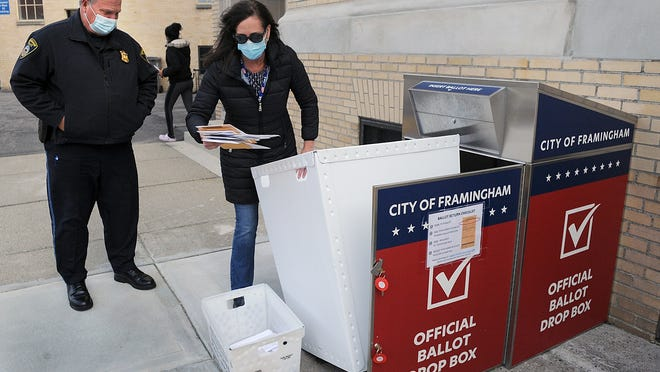 Framingham City Clerk Lisa Ferguson empties the official ballot drop box outside Citry Hall Monday afternoon with Framingham Police Officer James Green. The drop box will be sealed at 8 p.m. Monday, before Election Day.