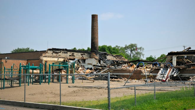 Debris from the Roosevelt Education Center in St. Cloud fire sits behind a fence July 10.