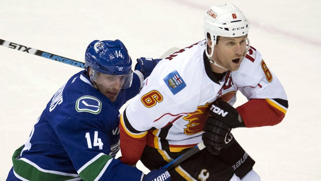 The NHL suspended Dennis Wideman, right, 20 games for cross-checking a linesman.