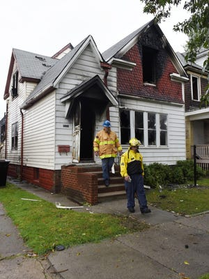 Sgt. David Sanders, foreground, and Detective James Kraszewski of the Detroit Police Department arson unit leave a house Thursday where a fire left one dead on the 3500 block of Rohns in Detroit.