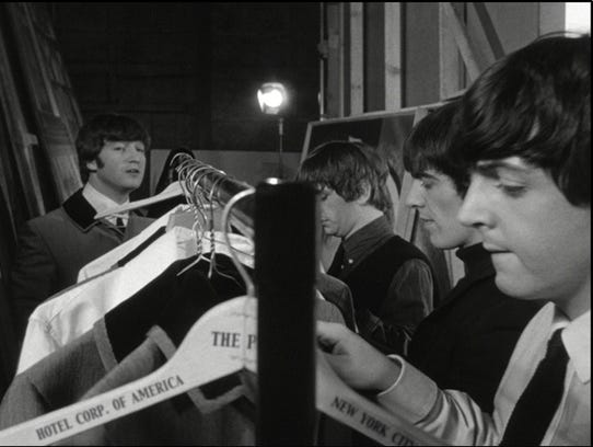 """All four Beatles standing by the clothes rack bearing their suits -- on the stolen Plaza Hotel hangers! The Beatles stayed at the Plaza Hotel in New York City for six nights in February 1964, departing finally on Friday February 21.  Just nine days later on Monday March 2, the Beatles started shooting their first film """"A Hard Day's Night"""" in London,  with four Plaza Hotel hangers on the film set!"""