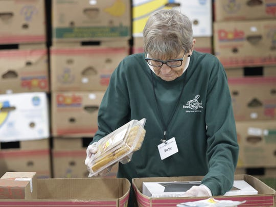 Volunteer Bevy VanDaalwyk packs baked goods at the St. Joseph Food Program in Menasha. Wm. Glasheen/USA TODAY NETWORK-Wisconsin.