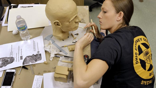 Forensic artist Samantha A.J. Molnar works on facial reconstructions Wednesday at the University of South Florida in Tampa.