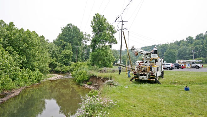 Dominion Power workers put in new poles along Jennings Branch in Churchville on Wednesday, June 10, 2015.