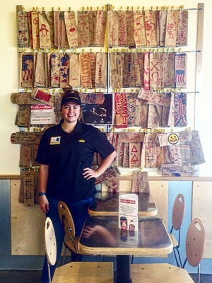 Katlyn Kirkwood, Flag Your Bag Ambassador at Which WIch, stands by some of the collected bags at the Hattiesburg store. After July 4, the bags will be filled with treats and sent to U.S. troops in Afghanistan.