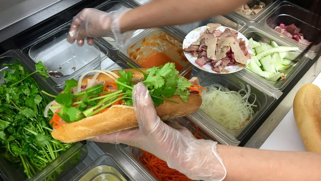 Lien Le loads fresh cilantro and quick-pickled vegetables onto a banh mi at Saigon Sandwiches.