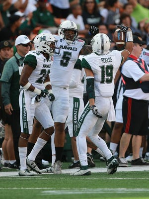 Hawaii defensive back Jalen Rogers (19) celebrates with defensive back Zach Wilson (20) and defensive lineman Makani Kema-Kaleiwahea (5) after he made an interception against Middle Tennessee on Dec. 24, 2016.