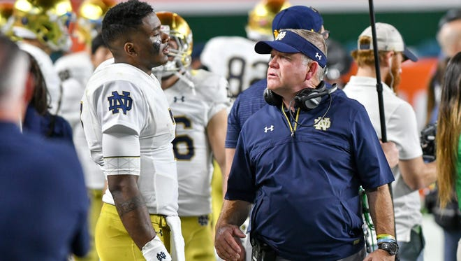 Notre Dame Fighting Irish head coach Brian Kelly talks to quarterback Brandon Wimbush (7) in the third quarter of the game against the Miami Hurricanes at Hard Rock Stadium.