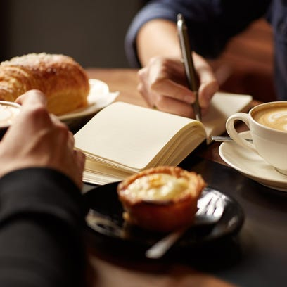 Table with coffee, pastries and one person taking notes
